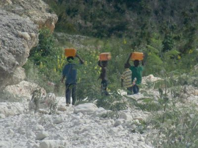 Young boys carrying water home. Children are now being found with hernia's, as it's their responsibility to fetch water. The weight is too much for their body, thus resulting in hernia's